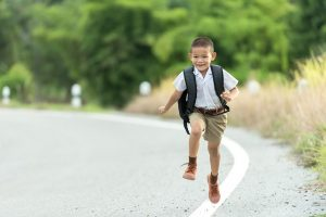 Happy kid running home with his backpack