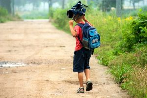 Boy walking to back to school with a backpack on his head