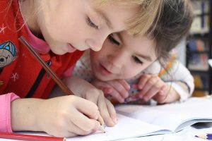 Two girls working together with a notebook going back to school
